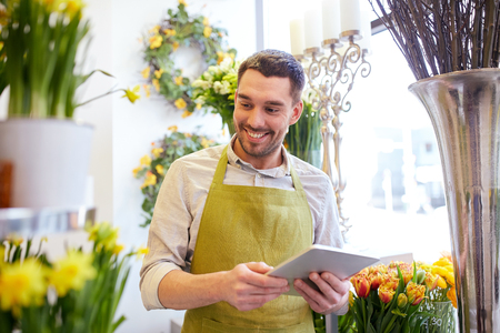 floristry: people, business, technology, sale and floristry and concept - happy smiling florist man with tablet pc computer at flower shop