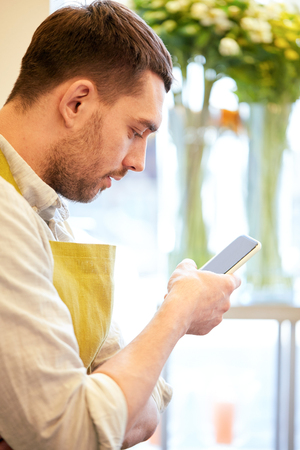 people, sale, retail, business and floristry concept - florist man texting on smartphone at flower shop