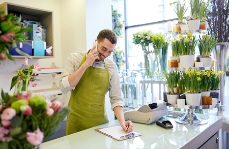 floristry: people, sale, retail, business and floristry concept - happy smiling florist man calling on smartphone and making notes to clipboard at flower shop counter Stock Photo