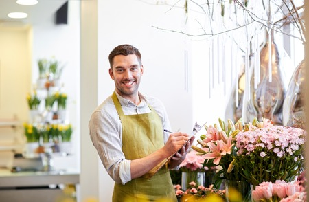 floristry: people, sale, retail, business and floristry concept - happy smiling florist man with clipboard writing and making notes order at flower shop