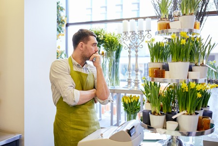 floristry: people, sale, retail, business and floristry concept - sad florist man with cashbox standing at flower shop counter