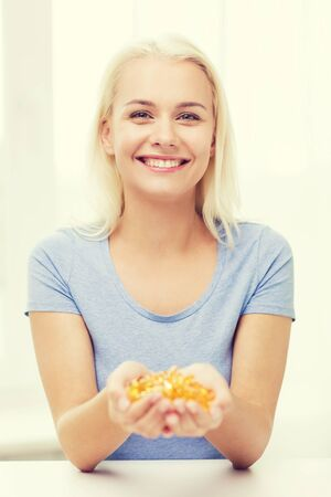 home health care: healthy eating, medicine, health care, food supplements and people concept - happy woman holding handful of fish oil capsules at home Stock Photo