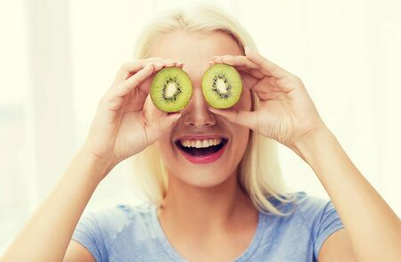 woman eat: healthy eating, organic food, fruit diet, comic and people concept - happy woman having fun and covering her eyes with kiwi Stock Photo