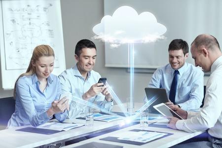 Negocio, la gente, el cloud computing y el concepto de tecnología - sonriendo equipo de negocios con los teléfonos inteligentes, computadoras tablet pc trabaja en la oficina Foto de archivo - 61235635