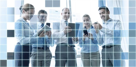 business technology: business, teamwork, people and technology concept - business team with tablet pc and smartphones meeting in office over blue squared grid background