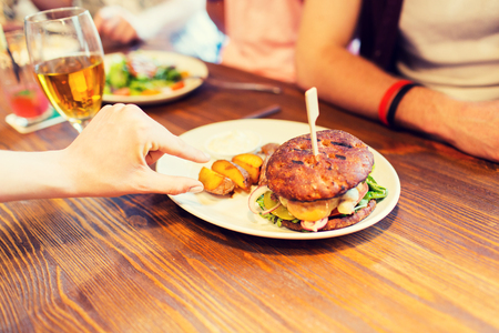 pubs: people, leisure, friendship, eating and food concept - close up of friends hands with burger at bar or pub Stock Photo