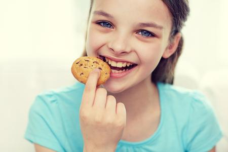 mensen, gelukkige kinderjaren, voedsel, snoepjes en bakkerijconcept - glimlachend meisje die koekje of koekje eten