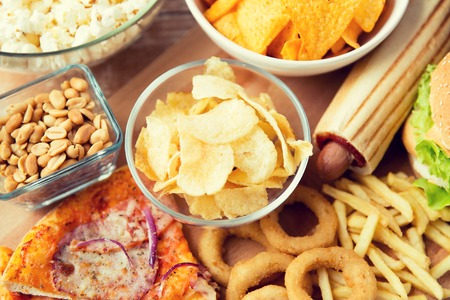 eating food: fast food and unhealthy eating concept - close up of different fast food snacks on wooden table Stock Photo