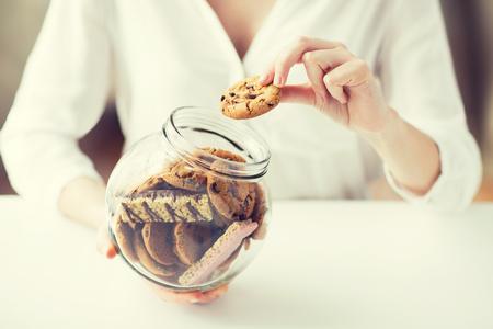 la gente, la comida basura, culinaria, el bicarbonato y el concepto de alimentación poco saludable - cerca de las manos con las galletas de avena de chocolate y barritas de muesli en el tarro de cristal Foto de archivo