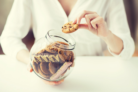filling out: people, junk food, culinary, baking and unhealthy eating concept - close up of hands with chocolate oatmeal cookies and muesli bars in glass jar