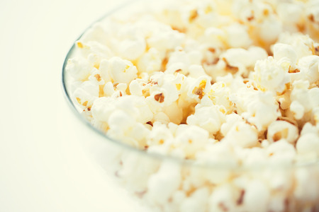 junkfood: fast food, junk-food and unhealthy eating concept - close up of popcorn in glass bowl