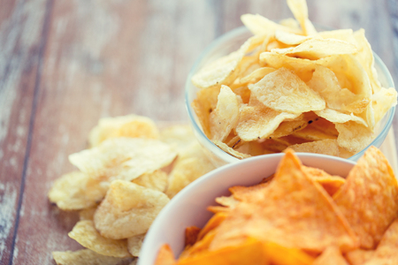 fast food, junk-food, cuisine and eating concept - close up of potato crisps and corn nachos in bowls on table Stock Photo