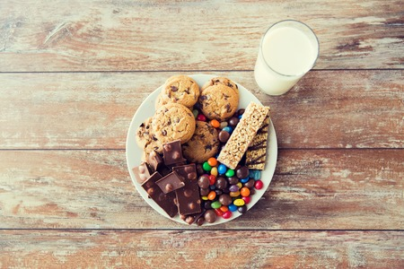 kitchen table top: junk food, sweets and unhealthy eating concept - close up of candies, chocolate, muesli and cookies with milk glass on plate
