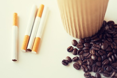 bad habits: bad habits, addiction and unhealthy lifestyle concept - close up of cigarettes, coffee cup and beans on table