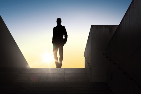 business and people concept - silhouette of businessman standing on stairs over sun light background Banco de Imagens