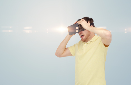 entertainment background: 3d technology, virtual reality, entertainment and people concept - happy young man with virtual reality headset or 3d glasses playing game over gray background