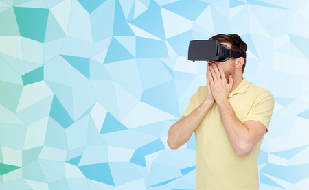 entertainment background: 3d technology, virtual reality, entertainment and people concept - amazed young man with virtual reality headset or 3d glasses playing game over low poly background Stock Photo