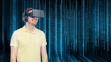 3d technology, virtual reality, programming, entertainment and people concept - happy young man with virtual reality headset or 3d glasses over blue binary code numbers and black background Stock Photo