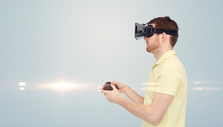 mediated: 3d technology, virtual reality, entertainment and people concept - happy young man with virtual reality headset or 3d glasses playing with game controller gamepad over gray background