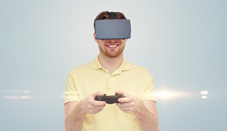 entertainment background: 3d technology, virtual reality, entertainment and people concept - happy young man with virtual reality headset or 3d glasses playing with game controller gamepad over gray background