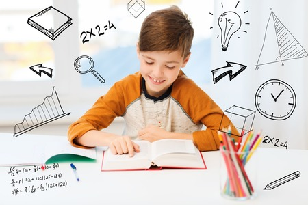 homework student: education, childhood, people, homework and school concept - happy student boy reading book or textbook at home over mathematical doodles