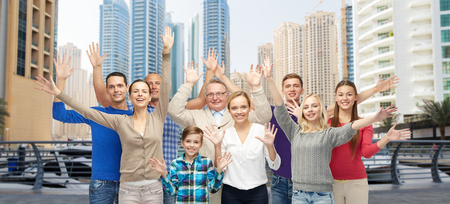 travel background: family, travel, tourism and people concept - group of smiling men, women and boy having fun and waving hands over dubai city street background Stock Photo