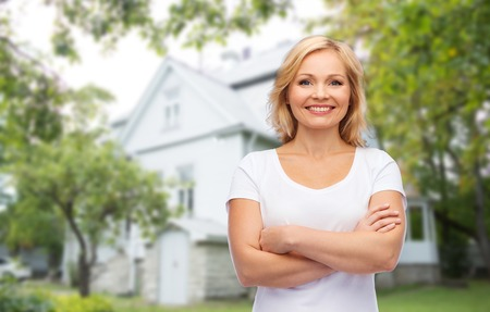 nice accommodations: real estate, home and people concept - smiling woman in blank white t-shirt with crossed arms over private house background