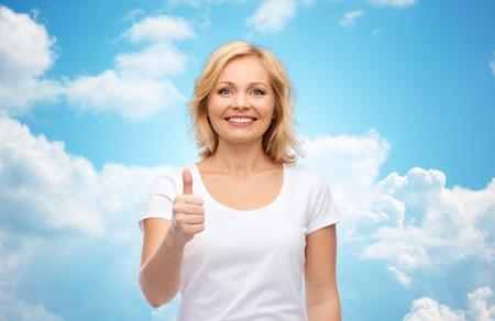 himmel wolken: Geste, Werbung und Menschen Konzept - lächelnde Frau in leeren weißen T-Shirt zeigt Daumen hoch über blauen Himmel und Wolken Hintergrund Lizenzfreie Bilder