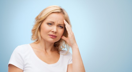 megrim: people, healthcare, stress and problem concept - unhappy woman suffering from headache over blue background Stock Photo