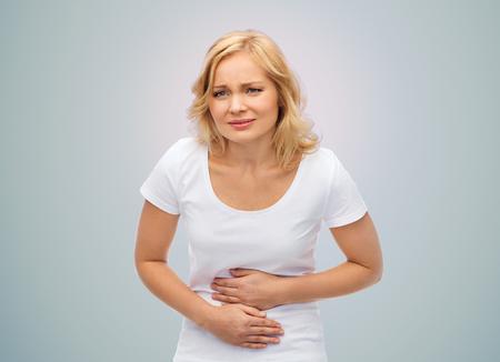 人々 のヘルスケアそして問題のコンセプト - 灰色の背景の上に胃の痛みから苦しんでいる不幸な女性 写真素材 - 61236410
