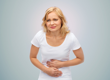 people, healthcare and problem concept - unhappy woman suffering from stomach ache over gray background Stockfoto
