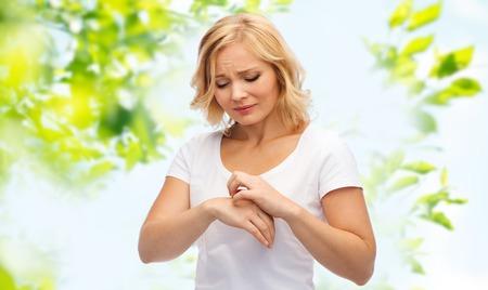 사람, 의료, 피부과, 알레르기 및 건강 문제 개념 - 녹색 자연 배경 위에 손을 인치 고통을 불행한 여자