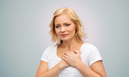 heart pain: people, healthcare, heart disease and problem concept - unhappy woman suffering from heartache over gray background