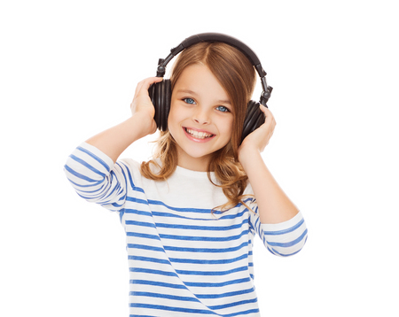 people, children and technology concept - smiling girl with headphones listening to music Banco de Imagens