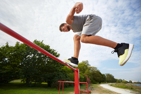 and the horizontal man: fitness, sport, exercising, training and lifestyle concept - young man jumping on horizontal bar outdoors