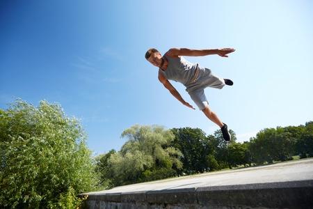hombre deportista: fitness, deporte, parkour y la gente concepto - joven saltando hombre en el parque de verano