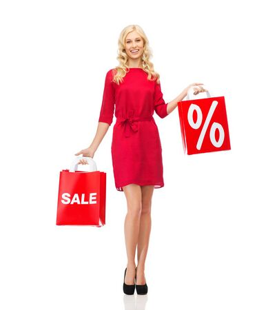 people, sale, discount and holidays concept - smiling woman in red dress with shopping bags Stock Photo