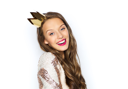 people, holidays and celebration concept - happy young woman or teen girl in party dress and princess crown Stock Photo