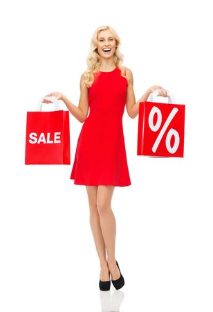 red dress: people, sale, discount and holidays concept - smiling woman in red dress with shopping bags Stock Photo