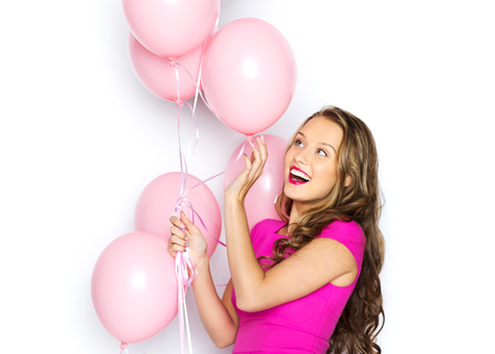 helium: beauty, people, style, holidays and fashion concept - happy young woman or teen girl in pink dress with helium air balloons