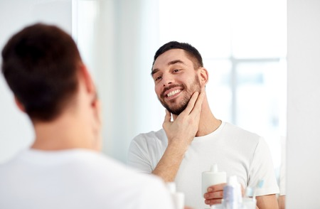 beauty, hygiene, shaving, grooming and people concept - smiling young man looking to mirror and applying aftershave at home bathroom Stock Photo