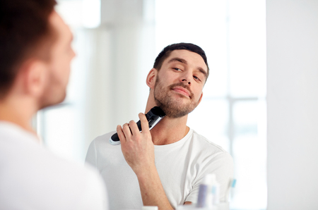 electric trimmer: beauty, hygiene, shaving, grooming and people concept - young man looking to mirror and shaving beard with trimmer or electric shaver at home bathroom