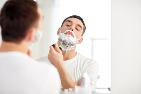 metrosexual: beauty, hygiene, shaving, grooming and people concept - young man looking to mirror and shaving beard with manual razor blade at home bathroom