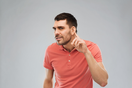 gesture and people concept - latin man having hearing problem listening to something