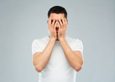 stupidity: people, crisis, emotions and stress concept - man in white t-shirt covering his face with hands over gray background