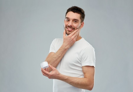 beauty, skin care, body care and people concept - smiling young man applying cream to face over gray background 스톡 콘텐츠