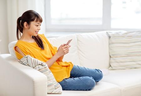 mujer alegre: las personas, la tecnología, la comunicación y el concepto de ocio - feliz mujer asiática joven que se sienta en el sofá y mensajes de texto mensaje en el teléfono inteligente en el hogar Foto de archivo