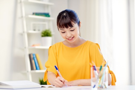essay: people, education, high school and learning concept - happy asian young woman student with book and notepad writing at home Stock Photo