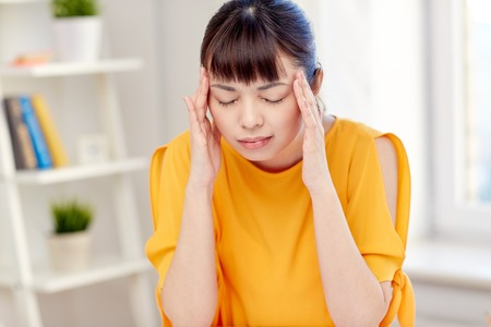 stress woman: people, healthcare, stress and problem concept - unhappy asian young woman suffering from headache at home