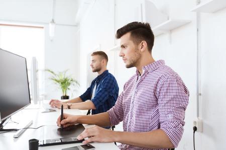 business, technologie, design en mensen concept - jonge creatieve man of ontwerper met computer en pentablet werken op kantoor